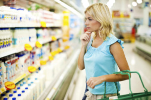 Woman shopping dairy food in food store.